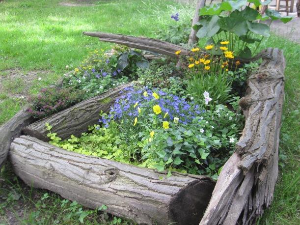Blumenbeet eingefasst mit Baumstämmen, die auf dem Gelände rumlagen